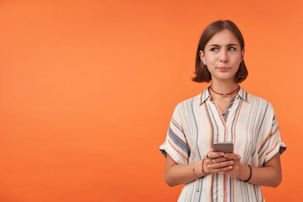 Ragazza giovane pensando in possesso di uno smartphone, fare una scelta, indossando maglietta a righe, bretelle e braccialetti per i denti.
