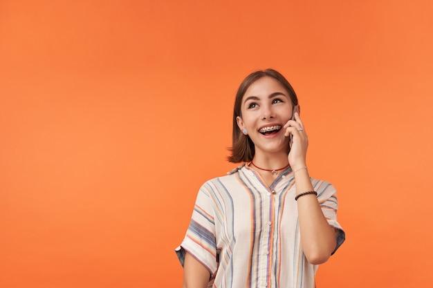 Ragazza che pensa e parla su uno smartphone. indossare magliette a righe, bretelle e braccialetti per i denti. in piedi sul muro arancione, sorridi e guarda nell'angolo in alto a sinistra dello spazio della copia