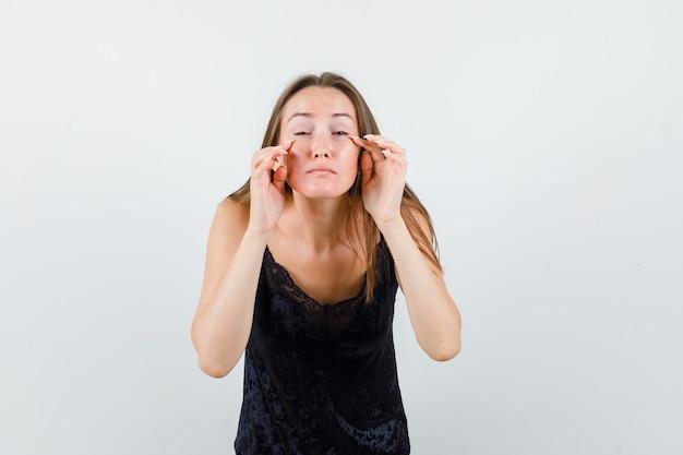 Молодая девушка, касаясь ее мешков под глазами в черном вид спереди синглет.
