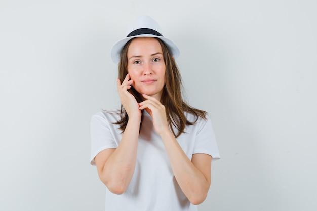 Молодая девушка трогает кожу лица в белой футболке и выглядит нежной