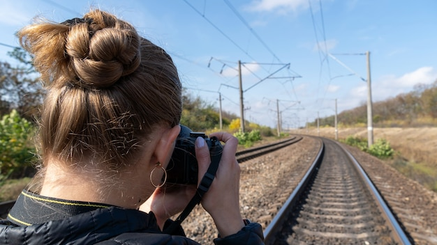 Молодая девушка турист на железной дороге фотографирует
