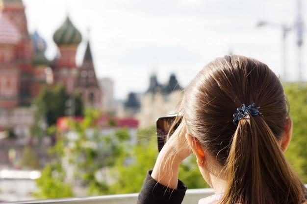 Молодая девушка туристические фотографии на смартфоне с видом на москву, собор василия блаженного, красную площадь