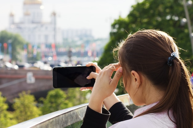 Молодая девушка туристических фотографий на смартфоне с видом на москву