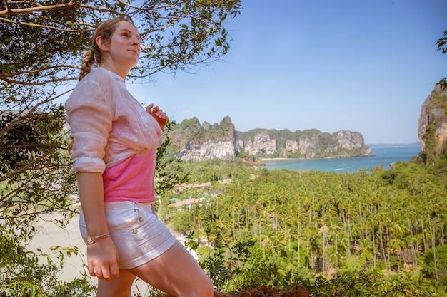 어린 소녀 관광객은 열대 해변과 정글이 내려다보이는 산 꼭대기에 서서 멀리 바라보고 있다
