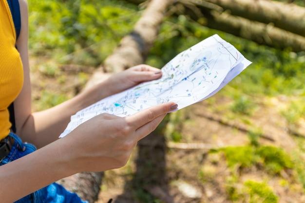Молодая девушка турист с синим рюкзаком держит карту маршрута, сидя на бревне в лесу