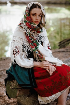 Young girl in a traditional embroidered dress sitting on a bench near the lake