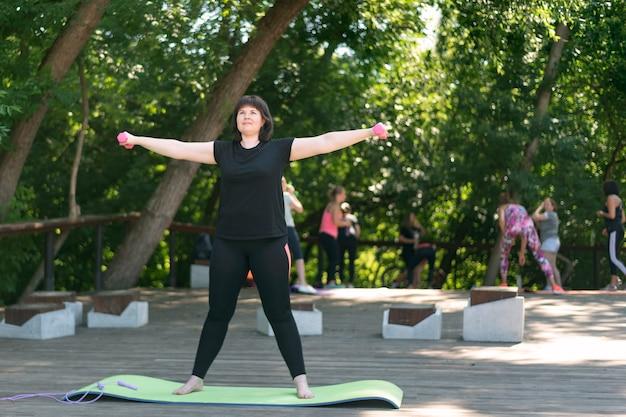 어린 소녀 트레이너는 공원에서 야외에서 아령으로 운동하는 것을 보여줍니다. 아령으로 손으로 원형 회전.
