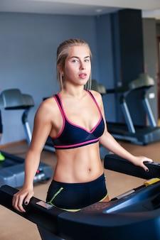 Молодая девушка тренируется в тренажерном зале на беговой дорожке