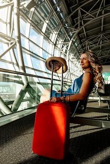 空港でホールドスーツケースを持って歩く少女旅行。観光コンセプト。