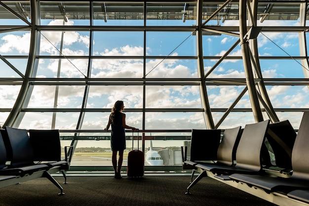 空港でホールドスーツケースを持って歩く少女旅行。観光コンセプト。 Premium写真