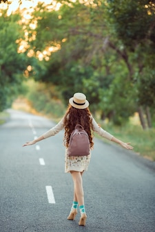 若い女の子の旅行者は旅行を楽しんでいます。道を歩いている幸せな女性。