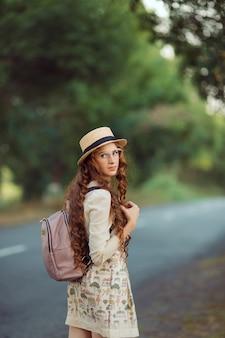 若い女の子の旅行者は徒歩で旅行を楽しんでいます。道路を帽子とバックパックを持って歩き、カメラを見ている幸せな女性の肖像画。