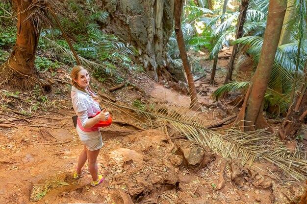 若い女の子の旅行者は、熱帯のジャングルの親指でヤシの木と茂みの高地の周りに立っています