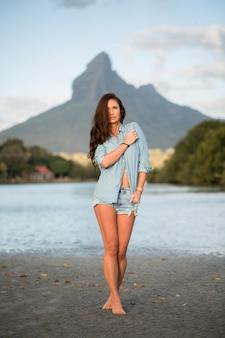 若い女の子の旅行者は山の反対側のビーチに立って、海の風景の美しさを楽しんでいます。若い女の子は野生生物、旅行、自由が大好きです。