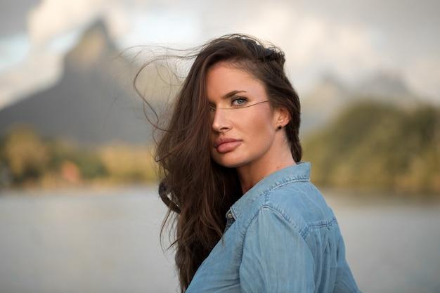 Молодая девушка-путешественница стоит на пляже напротив горы и наслаждается красотой морского пейзажа. молодая девушка любит дикую жизнь, путешествия, свободу.