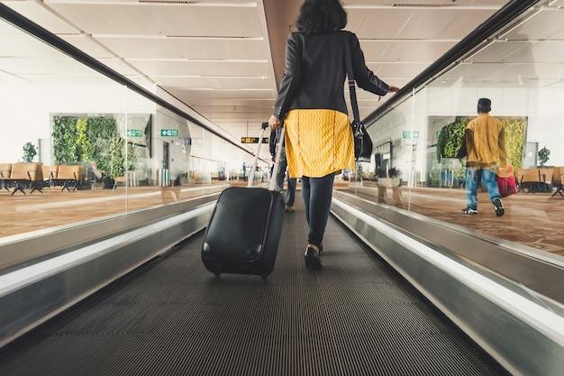 空港でホールドスーツケースを持って歩いている若い女の子の旅行者。ツーリストコンセプト。エスカレーター、インドの浦東空港の内部。