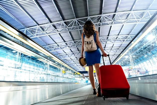 空港でホールドスーツケースを持って歩いている若い女の子の旅行者。観光コンセプト。