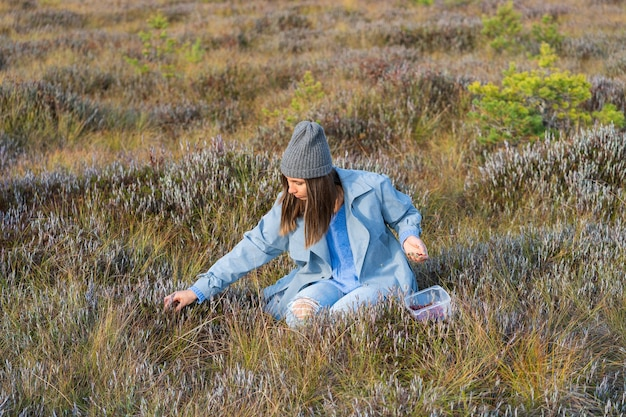 Young girl in trendy clothes picking cranberries enjoying sunny autumn weather fall in countryside