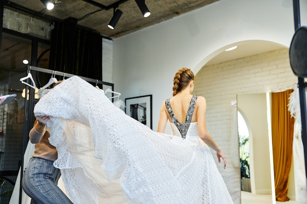 Young girl tries on a wedding dress in the bridal salon