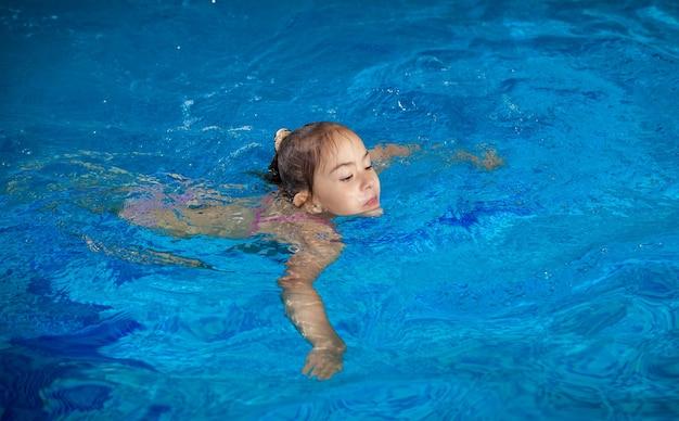 수영장에서 물 표면에 잡으려고 어린 소녀