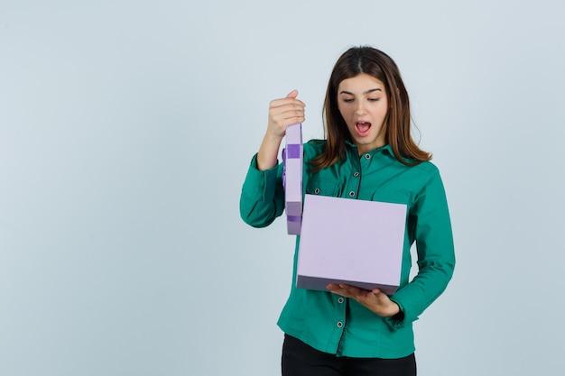 Молодая девушка пытается открыть подарочную коробку в зеленой блузке, черных штанах и выглядит удивленно. передний план.