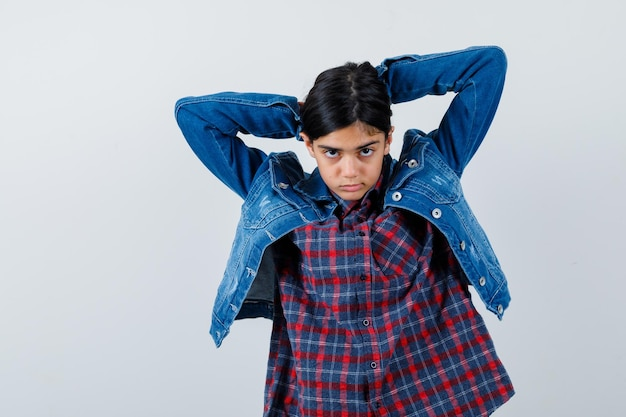 Молодая девушка заправляет волосы в клетчатую рубашку и джинсовую куртку и выглядит красивой.