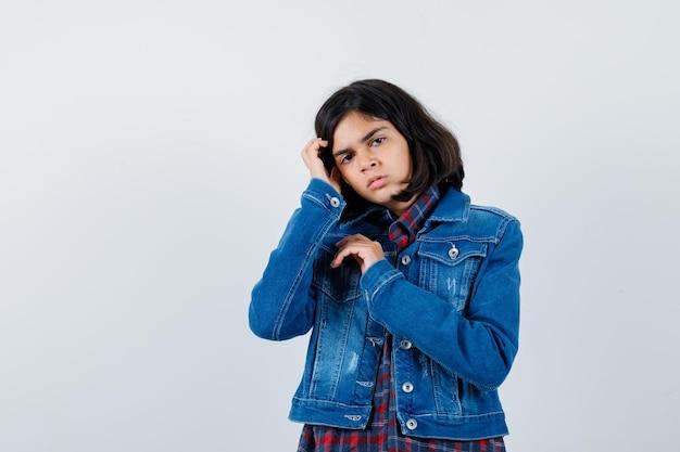 체크 셔츠와 진 재킷에 손으로 머리를 잡아 당기고 예쁜 앞모습을 보이는 어린 소녀.