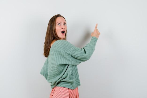 若い女の子が振り返り、人差し指で壁を指さし、ニットウェア、スカートで目をそらし、驚いた様子、正面図。