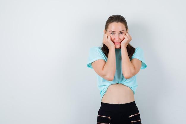 Giovane ragazza in t-shirt turchese, pantaloni appoggiati sulle guance sulle mani e dall'aspetto carino, vista frontale.