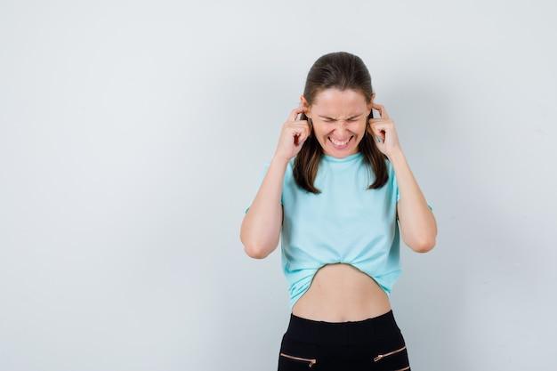 Giovane ragazza in maglietta turchese, pantaloni con le dita nelle orecchie e sguardo dispiaciuto, vista frontale.