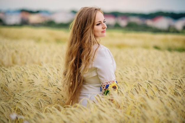 Young girl at ukrainian national dress posed at wreath field.