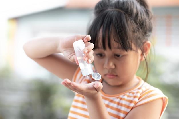 若い女の子はアルコールを使って手を洗う