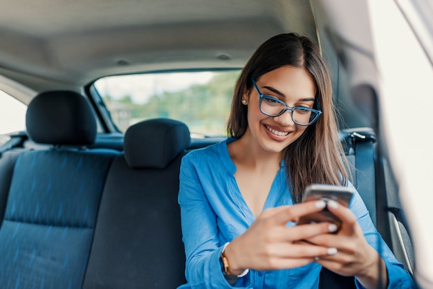 Young girl uses a mobile phone in the car. technology cell phone isolation