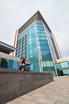 Young girl uses a smartphone on the office building