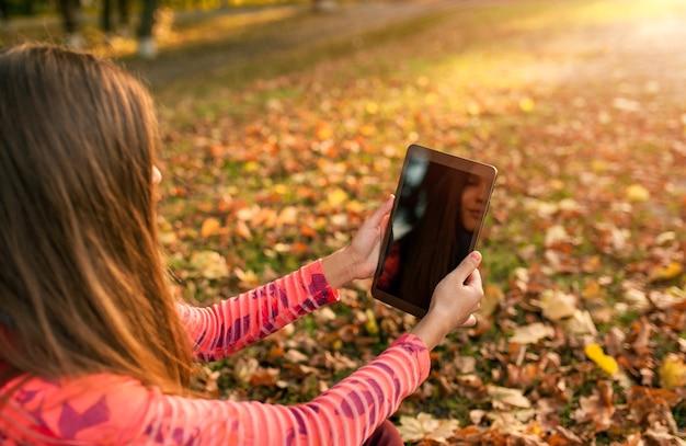 Молодая девушка с помощью планшета