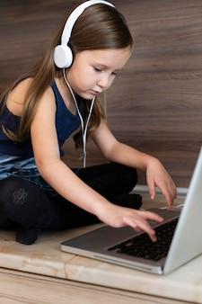 ヘッドフォンでラップトップを使用して若い女の子