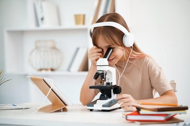 Молодая девушка с помощью микроскопа во время онлайн-урока дома