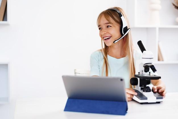 집에서 온라인 수업을 하는 동안 현미경을 사용하는 어린 소녀