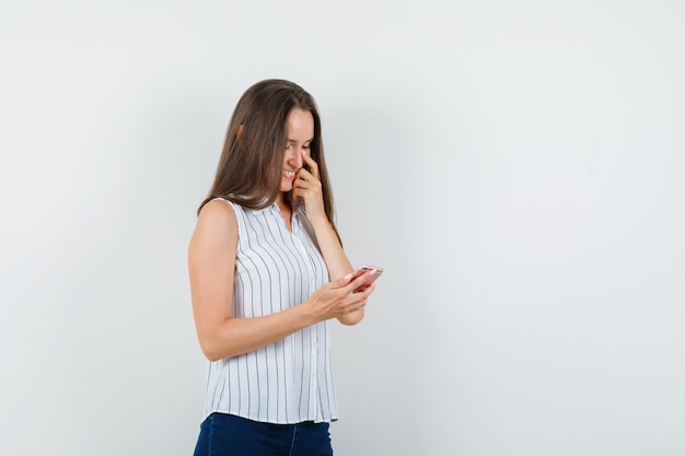 Young girl using mobile phone in t-shirt, jeans and looking joyful , front view.