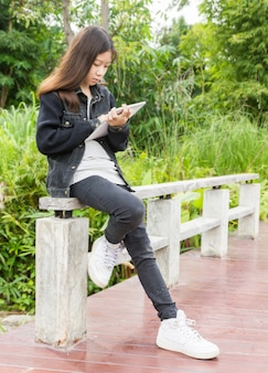 A young girl using tablet computer in park