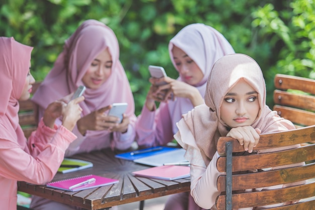 Young girl using their own smartphone and ignoring her friend