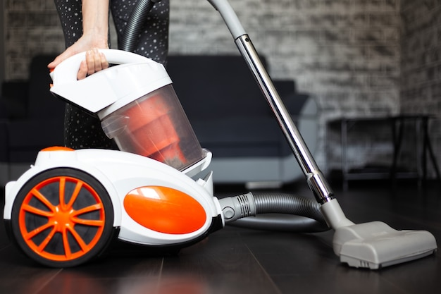 Young girl using vacuum cleaner for dark laminate.
