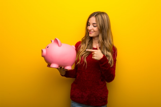 Young girl on vibrant yellow holding a piggybank