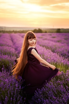 Young girl in violet dress having fun on sage flower field.
