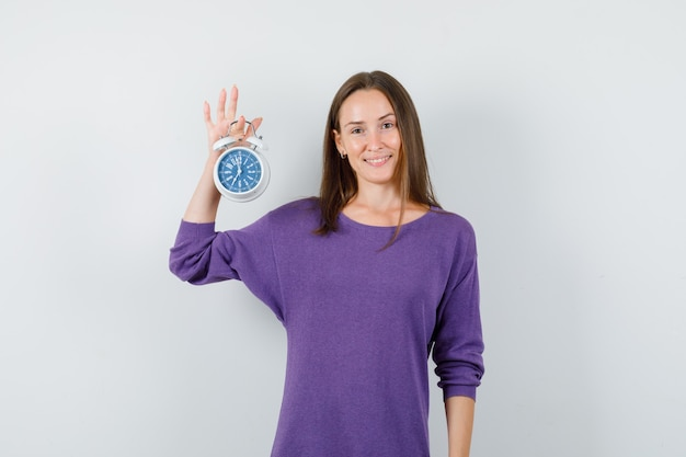 Young girl in violet shirt holding alarm clock and looking optimistic , front view.