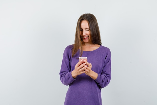 Young girl in violet shirt using mobile phone and looking cheerful , front view.