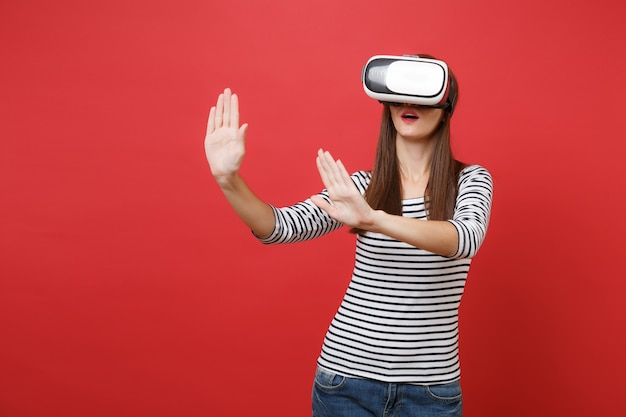 Young girl in virtual reality glasses touch something like push on button pointing at floating virtual screen isolated on red background. people sincere emotions lifestyle concept. mock up copy space.