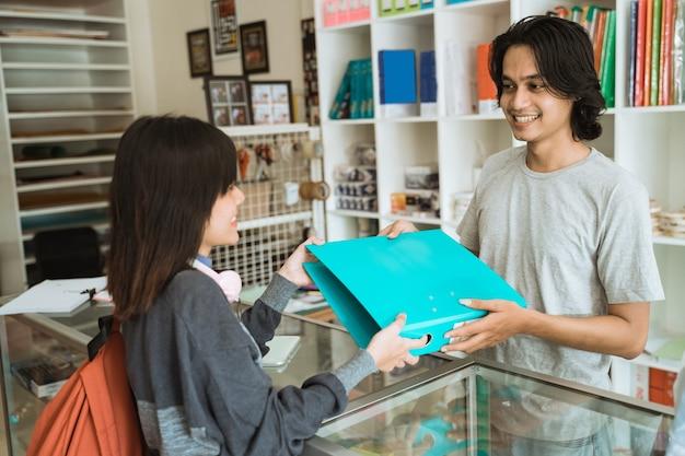 Молодая девушка, посещающая магазин канцелярских товаров, покупает канцелярские товары