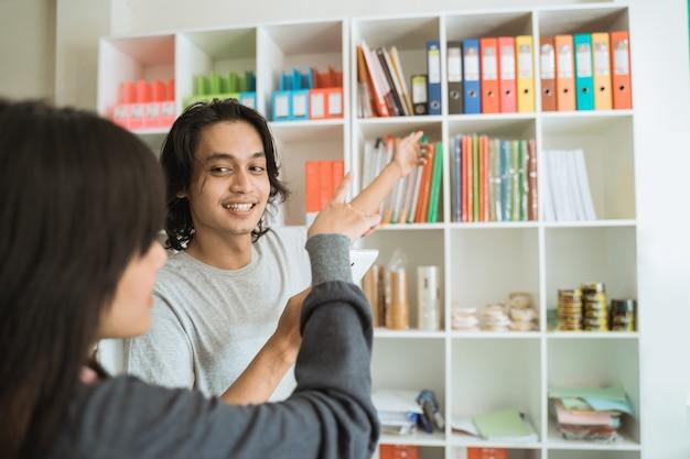 Молодая девушка посещает магазин канцелярских товаров, выбирая предмет