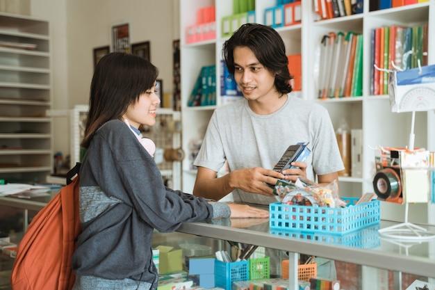 Молодая девушка, посещающая магазин канцелярских товаров, разговаривает с кассиром-мужчиной о ценах